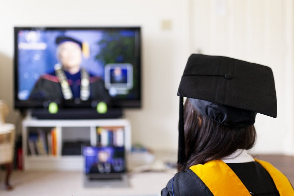 A university graduate wearing the cap and gown at home.