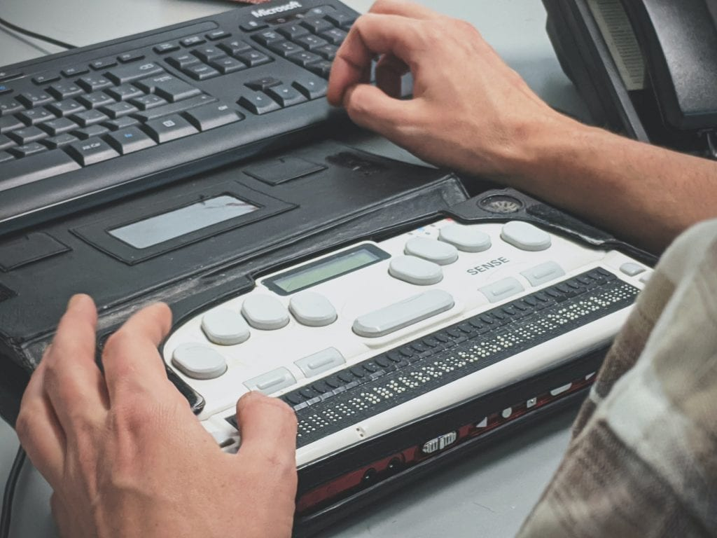 A man typing using a braille screen reader.